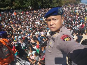 Chief Water Police of Lombok Dewa Wijaya takes a picture in front of hundreds of people attempting to leave the Gili Islands after an earthquake Gili Trawangan, in Lombok, Indonesia, August 6, 2018, in this picture obtained from social media. Indonesia Water Police/Handout/via REUTERS