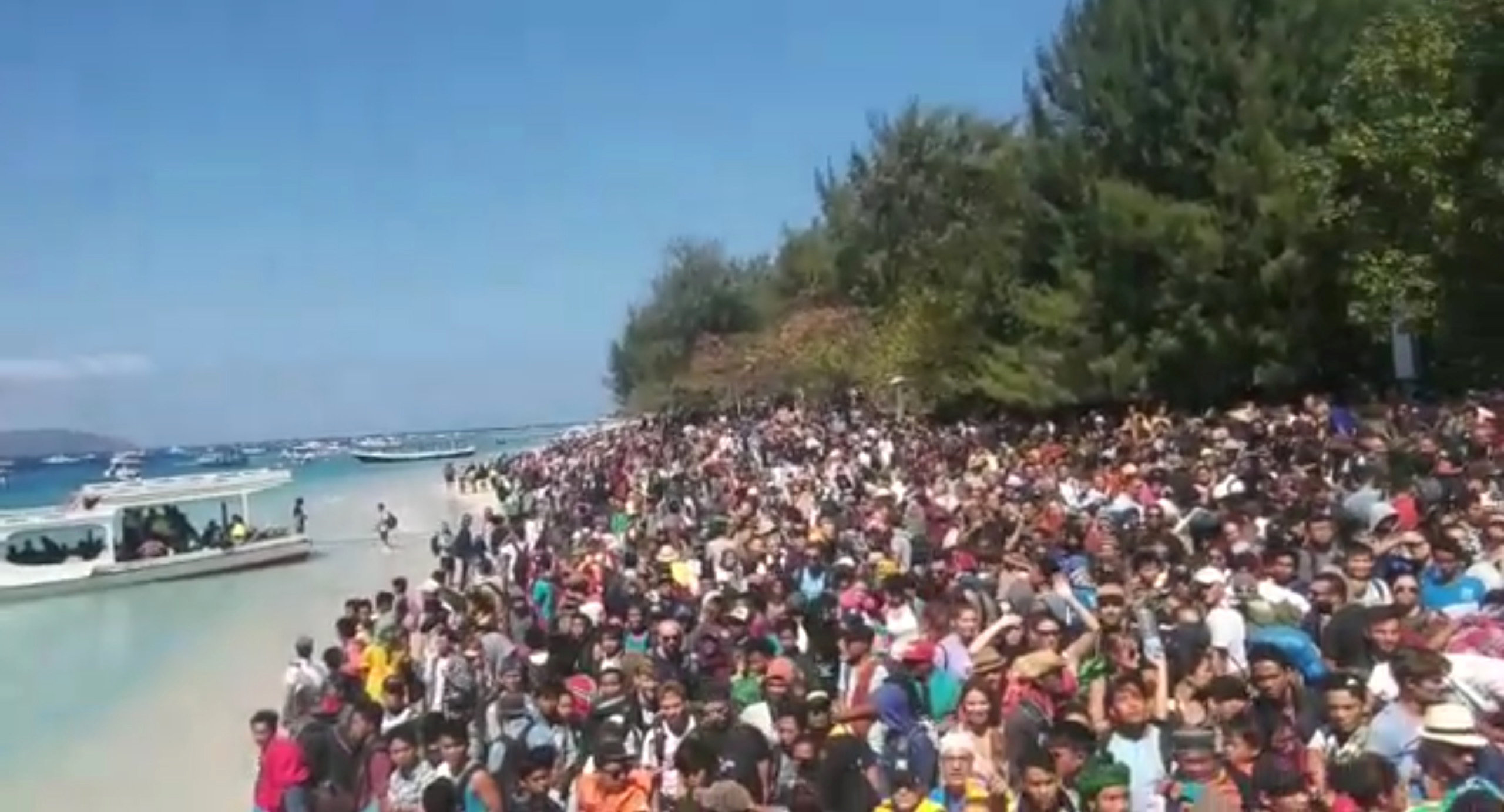 People crowd on the shore as they attempt to leave the Gili Islands after an earthquake Gili Trawangan, in Lombok, Indonesia, August 6, 2018, in this still image taken from a video. Indonesia Water Police/Handout/via REUTERS