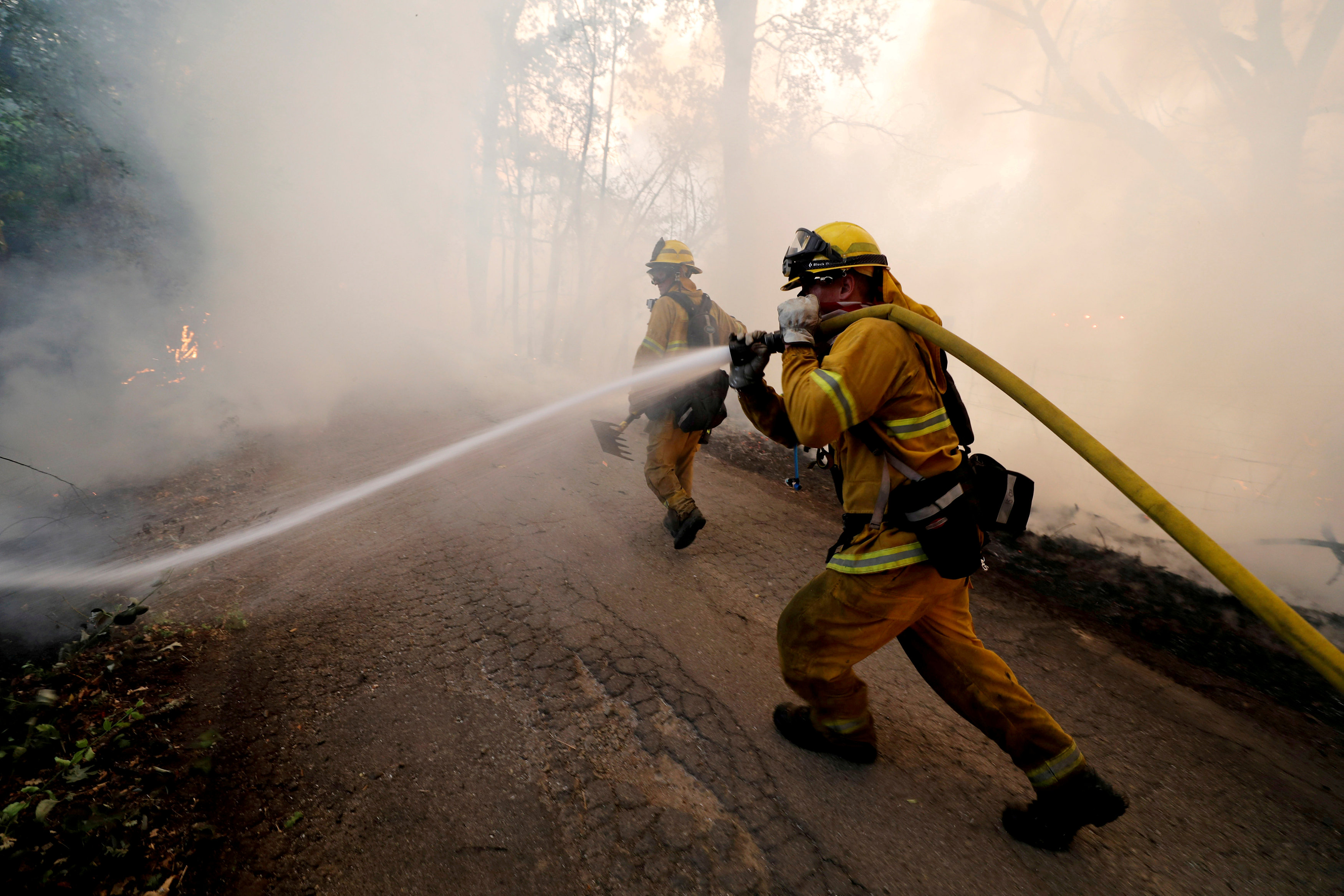 FILE PHOTO: A firefighter knocks down hotspots to slow the spread of the River Fire (Mendocino Complex) in Lakeport, California, U.S. July 31, 2018. REUTERS/Fred Greaves/File Photo