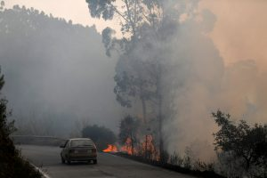 A car passes next to a fire near small village of Monchique, Portugal August 6, 2018. REUTERS/Rafael Marchante