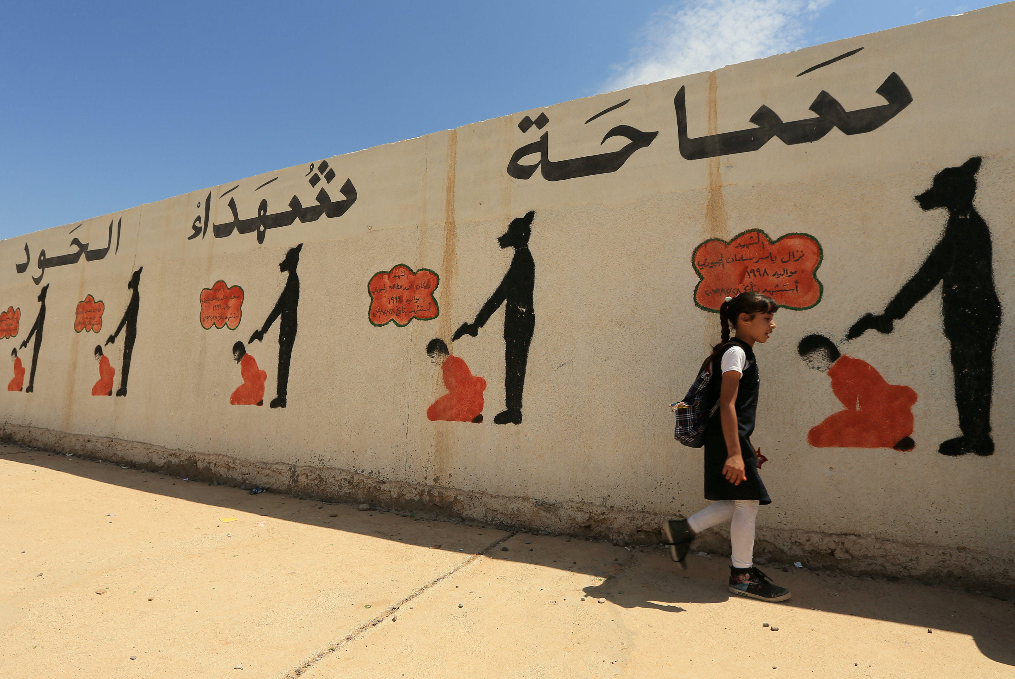 FILE PHOTO: An Iraqi student walks past a school wall covered with drawings showing how Islamic State militants executed their prisoners in Mosul, Iraq April 30, 2018. REUTERS/Ari Jalal/File Photo
