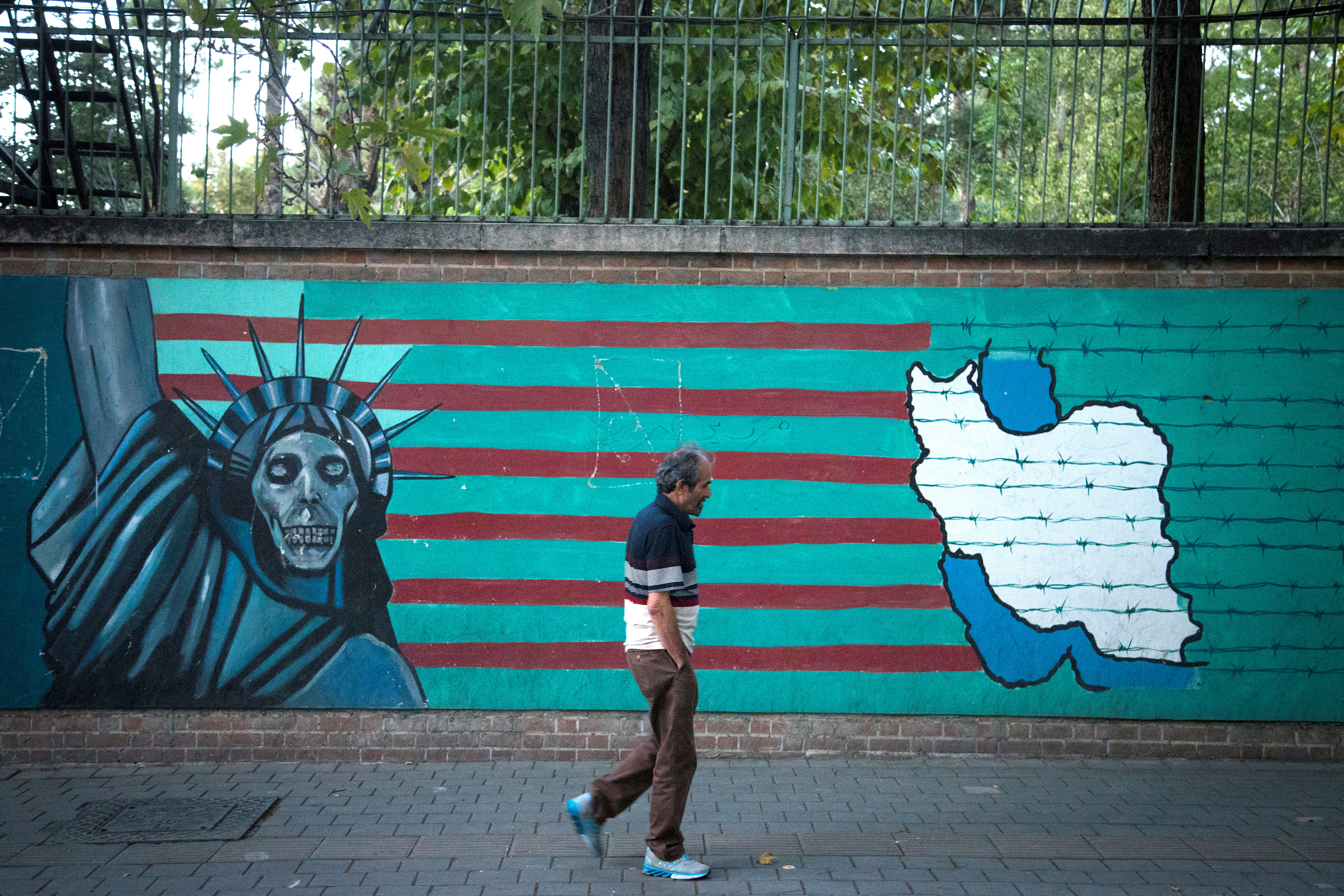 FILE PHOTO: A man walks past an anti-U.S. mural in Tehran, Iran October 13, 2017. Nazanin Tabatabaee Yazdi/TIMA via REUTERS