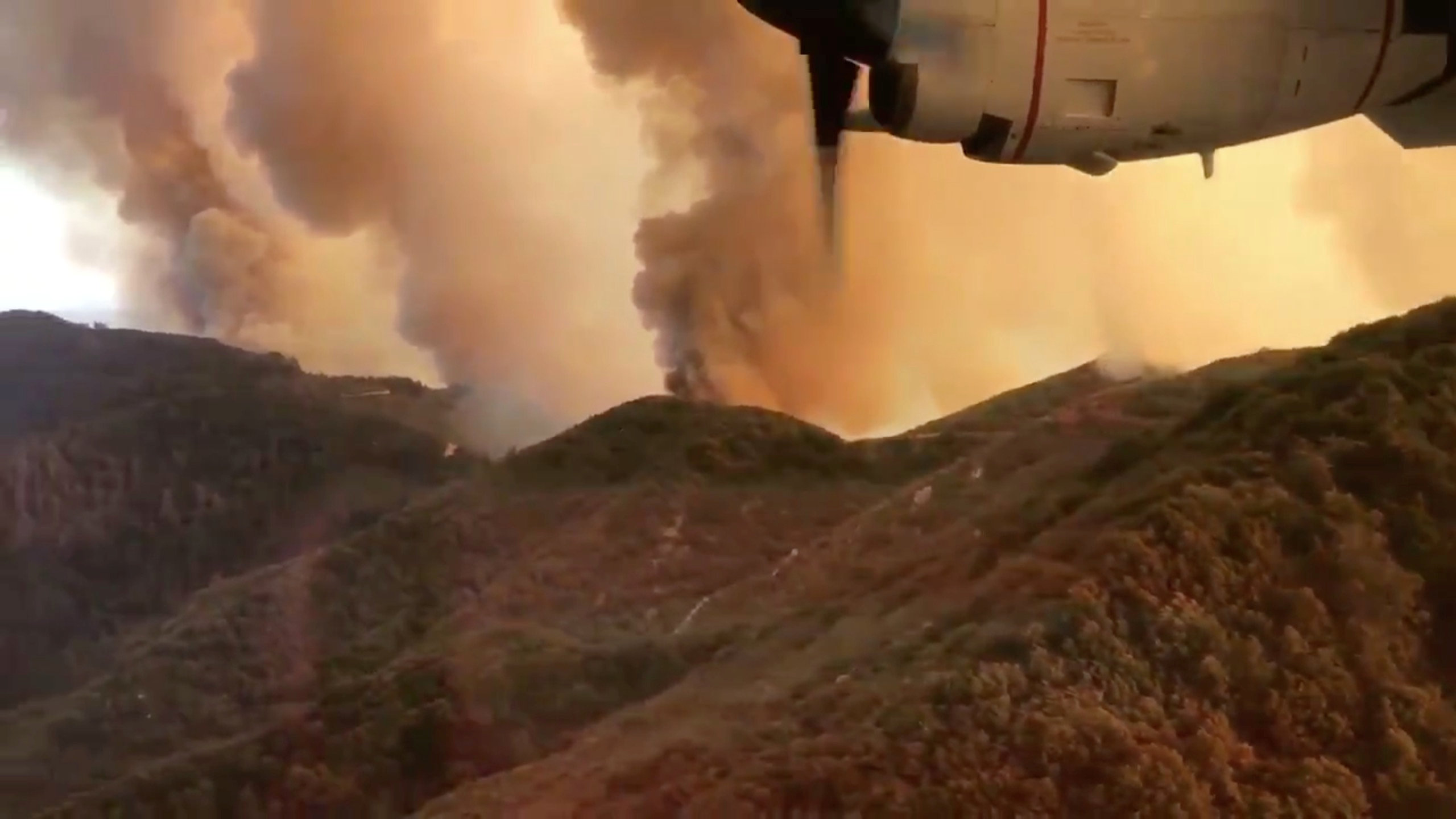 Aerial view of Trabuco Canyon as a tanker aircraft dumps load onto Holy Fire, Near Santiago Peak, California, U.S., August 6, 2018 in this still image taken from a video obtained from social media. TWITTER / @ZULUJUMPER/via REUTERS
