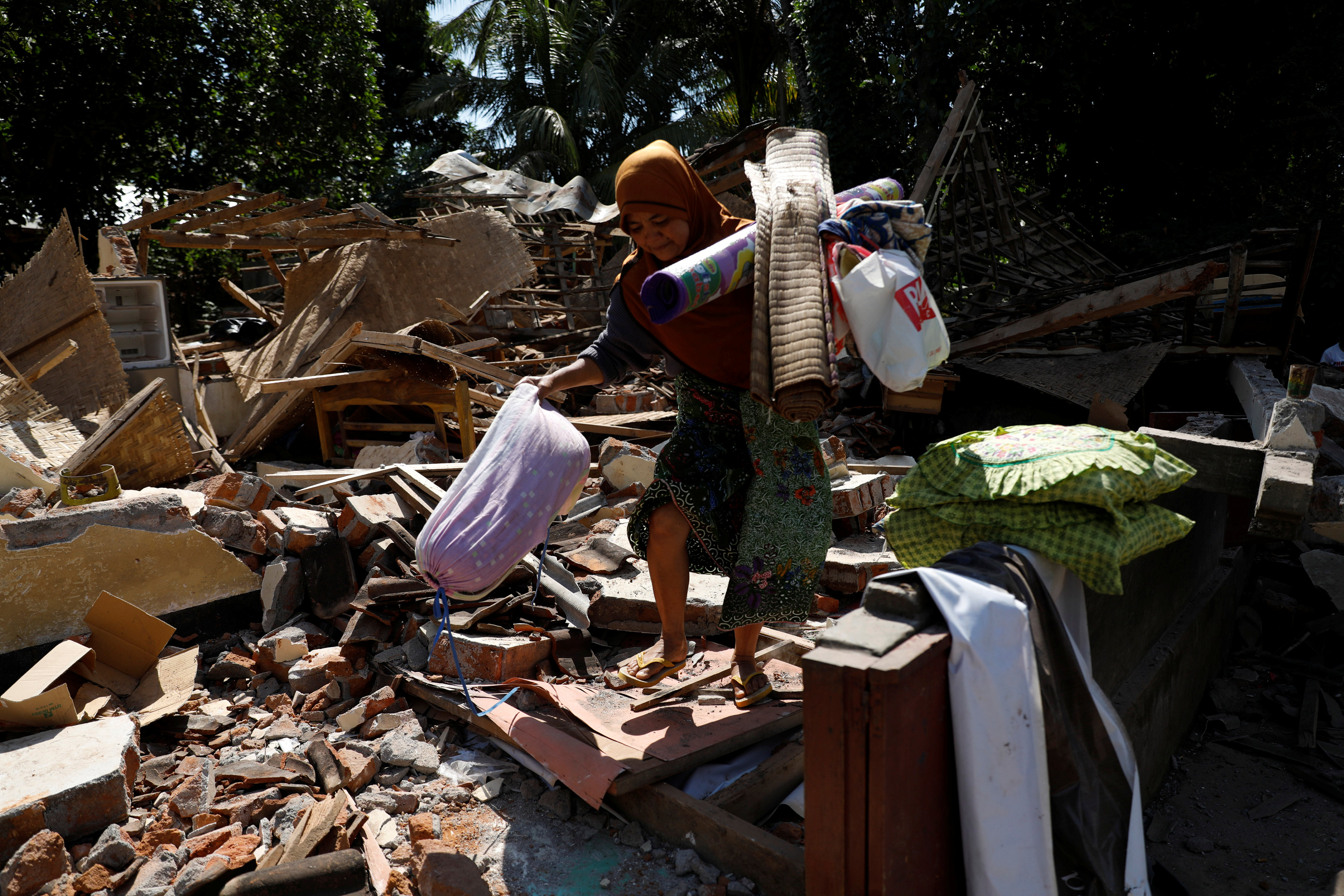 A woman carries valuable goods from the ruins of her house at Kayangan district after earthquake hit on Sunday in North Lombok, Indonesia, August 7, 2018. REUTERS/Beawihar