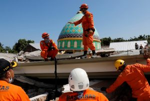 Rescuers and policemen talk on top of a collapsed mosque as they try to find survivors after an earthquake hit on Sunday in Pemenang, Lombok Island, Indonesia, August 7, 2018. REUTERS/Beawiharta