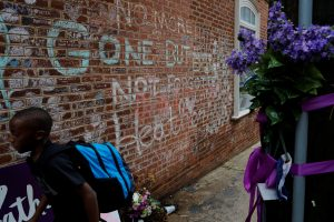 A boy passes tributes written at the site where Heather Heyer was killed during the 2017 white-nationalist rally in Charlottesville, Virginia, U.S., August 1, 2018. REUTERS/Brian Snyder