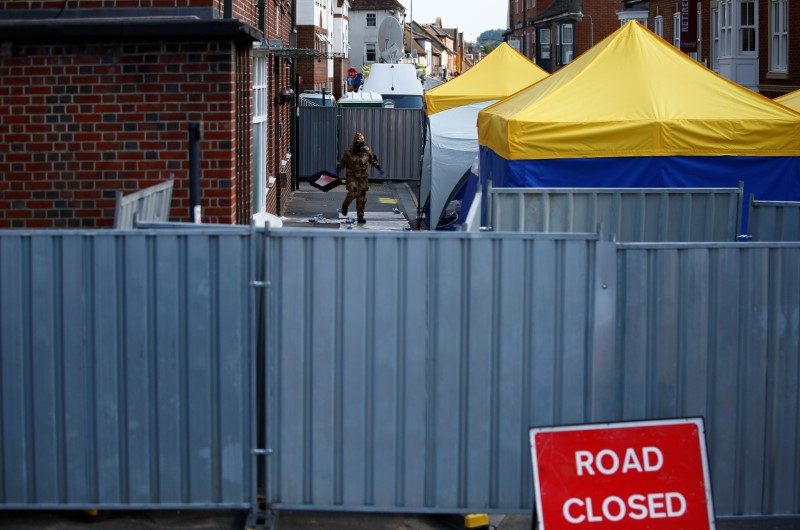 A forensic investigator, wearing a protective suit, emerges from the rear of John Baker House, after it was confirmed that two people had been poisoned with the nerve-agent Novichok, in Amesbury, Britain, July 6, 2018. REUTERS/Henry Nicholls