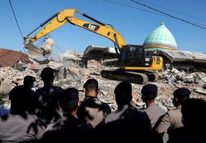 Policemen stand as heavy equipment move debris for try to find people trapped inside a mosque after an earthquake hit on Sunday in Pemenang, Lombok Island, Indonesia, August 8, 2018. REUTERS/Beawiharta