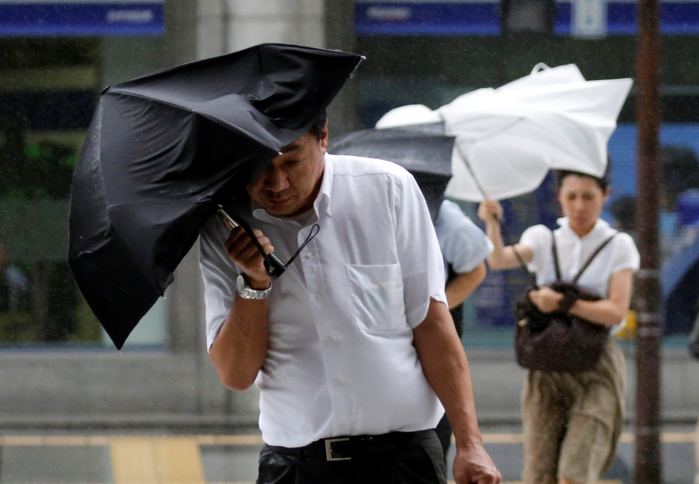 Passersby using an umbrella struggle against a heavy rain and wind as Typhoon Shanshan approaches Japan's mainland in Tokyo, Japan August 8, 2018. REUTERS/Toru Hanai