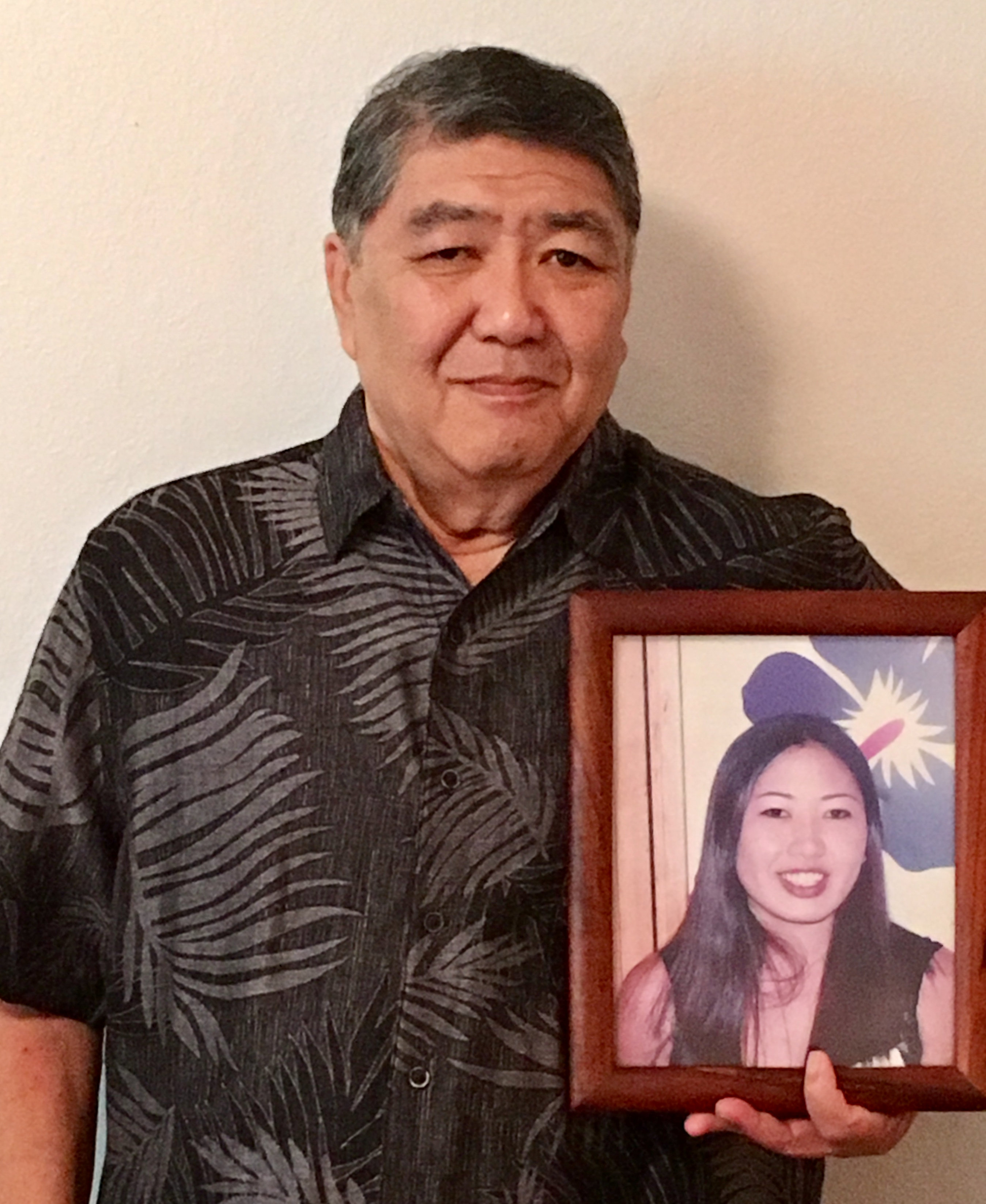 George Young holds a framed photo of his late daughter Tim Young in Hilo, Hawaii, U.S., July 30, 2018. Picture taken July 30, 2018. Courtesy Lynn Viale/Handout via REUTERS
