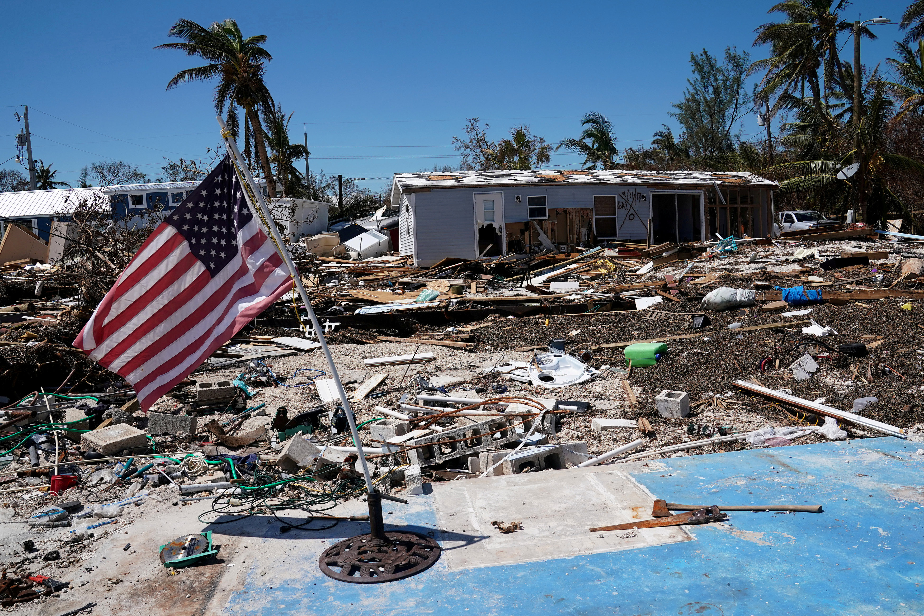 FILE PHOTO: A U.S. flag flies over a debris field of former houses following Hurricane Irma in Islamorada, Florida, U.S., September 15, 2017. REUTERS/Carlo Allegri/File Photo
