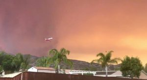 A plane flies off after dumping fire retardant over the Holy Fire close to a residential area in Lake Elsinore, California, the U.S. August 8, 2018 in this still image taken from a video obtained from social media. Camille Collins/via REUTERS