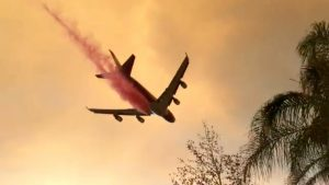 A plane dumps fire retardant over the Holy Fire as it spreads in Lake Elsinore, California, the U.S. August 8, 2018 in this still image taken from a video obtained from social media. Lake Elsinore City Hall/via REUTERS