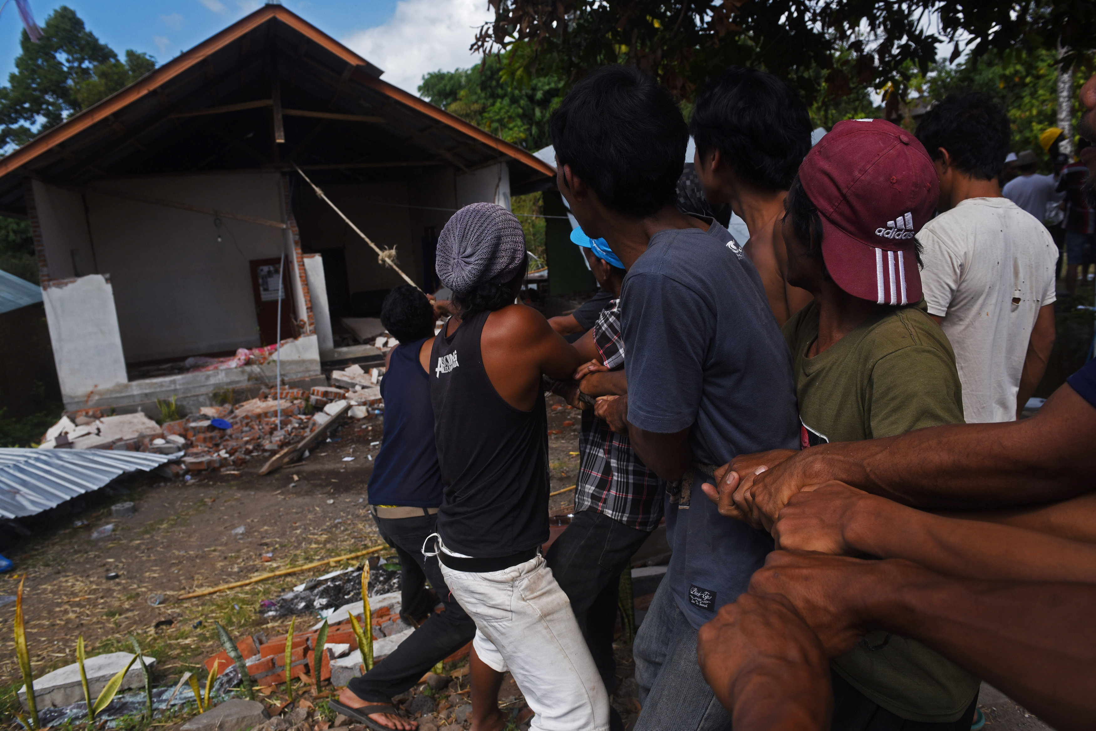 Residents pull down an earthquake damaged house in Kayangan, North Lombok, Indonesia August 12, 2018 in this photo taken by Antara Foto. Picture taken August 12, 2018. Antara Foto/Zabur Karuru/ via REUTERS