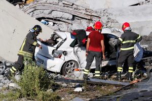 Firefighters inspect a crushed car at the collapsed Morandi Bridge site in the port city of Genoa, Italy August 14, 2018. REUTERS/Stefano Rellandini