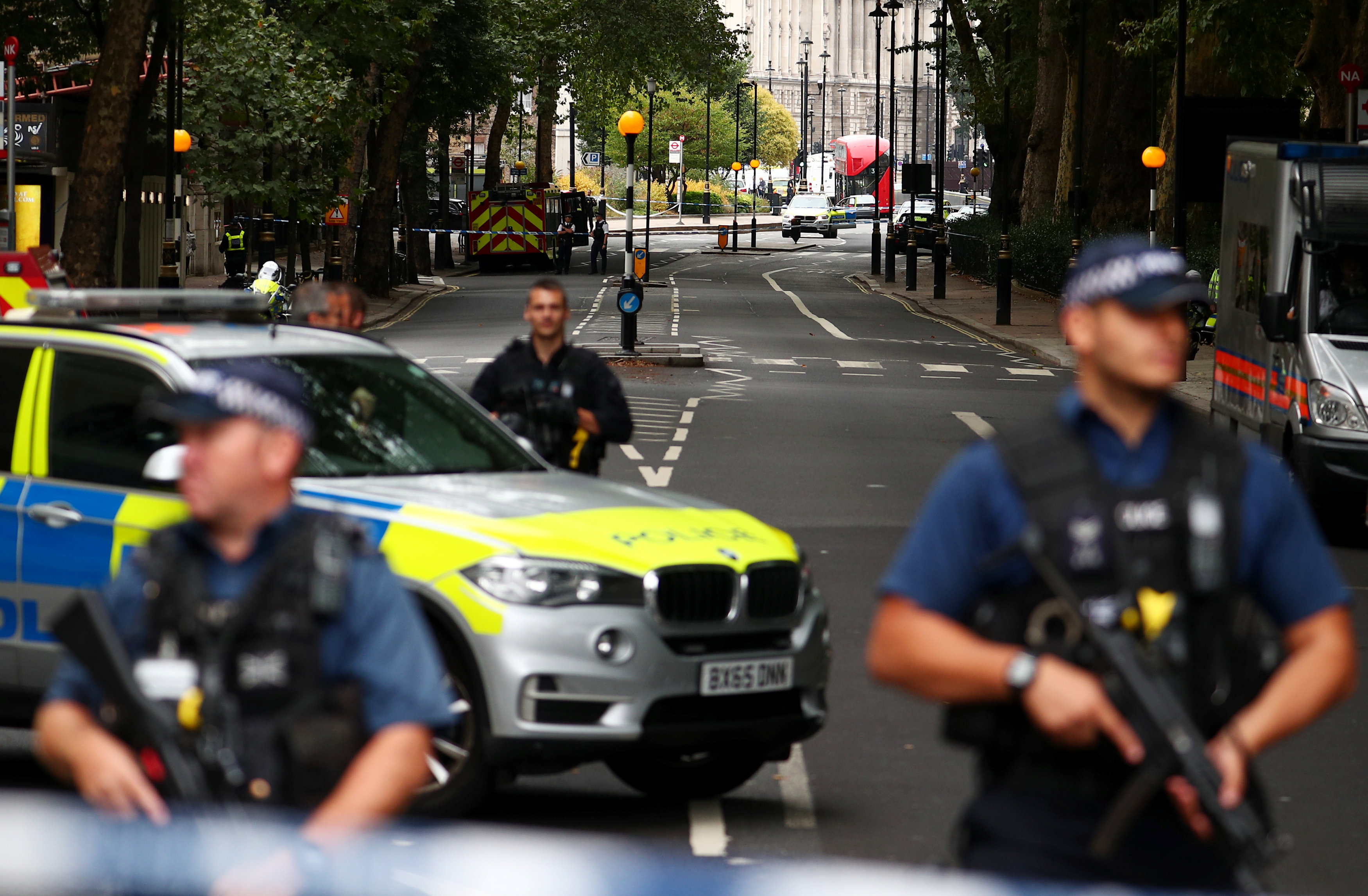 Armed police officers stand at a cordon after a car crashed outside the Houses of Parliament in Westminster, London, Britain, August 14, 2018. REUTERS/Hannah McKay