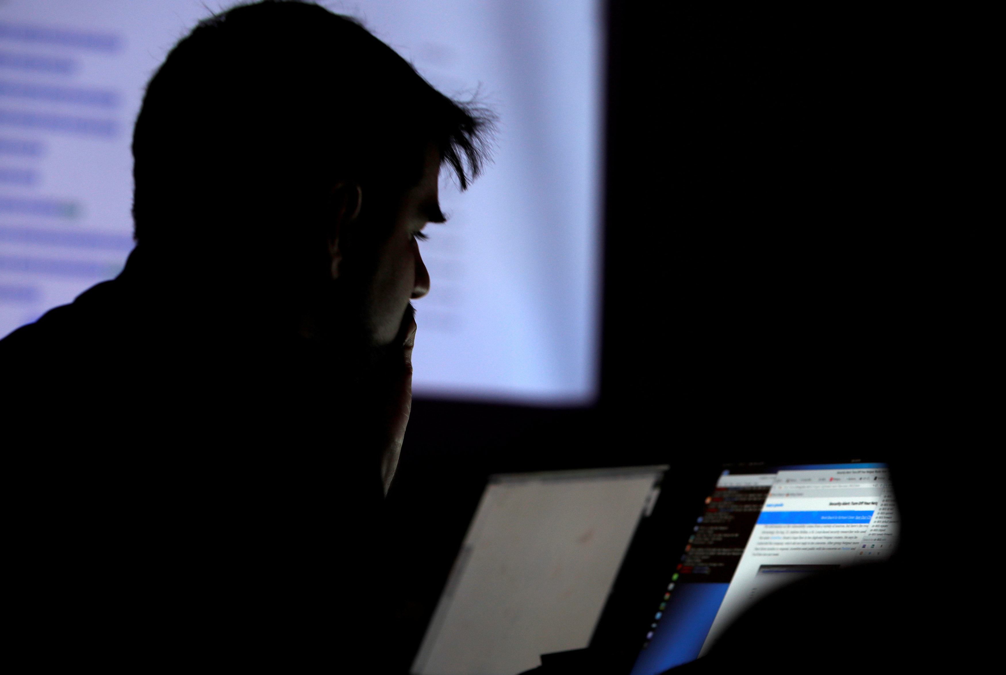 FILE PHOTO: A man takes part in a hacking contest during the Def Con hacker convention in Las Vegas, Nevada, U.S. on July 29, 2017. REUTERS/Steve Marcus/File Photo