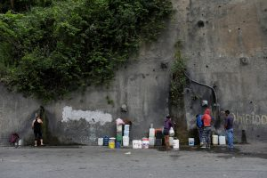 People fill containers with water coming from a mountain, in a road at Plan de Manzano slum in Caracas, Venezuela July 20, 2018. Picture taken July 20, 2018. REUTERS/Marco Bell