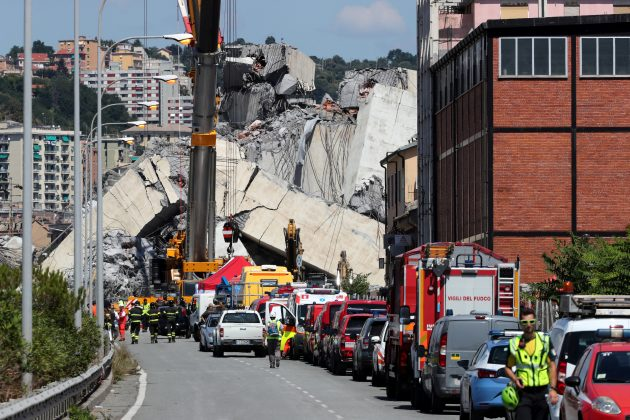 Firefighters and rescue workers stand at the site of a collapsed Morandi Bridge in the port city of Genoa, Italy August 15, 2018. REUTERS/Stefano Rellandini