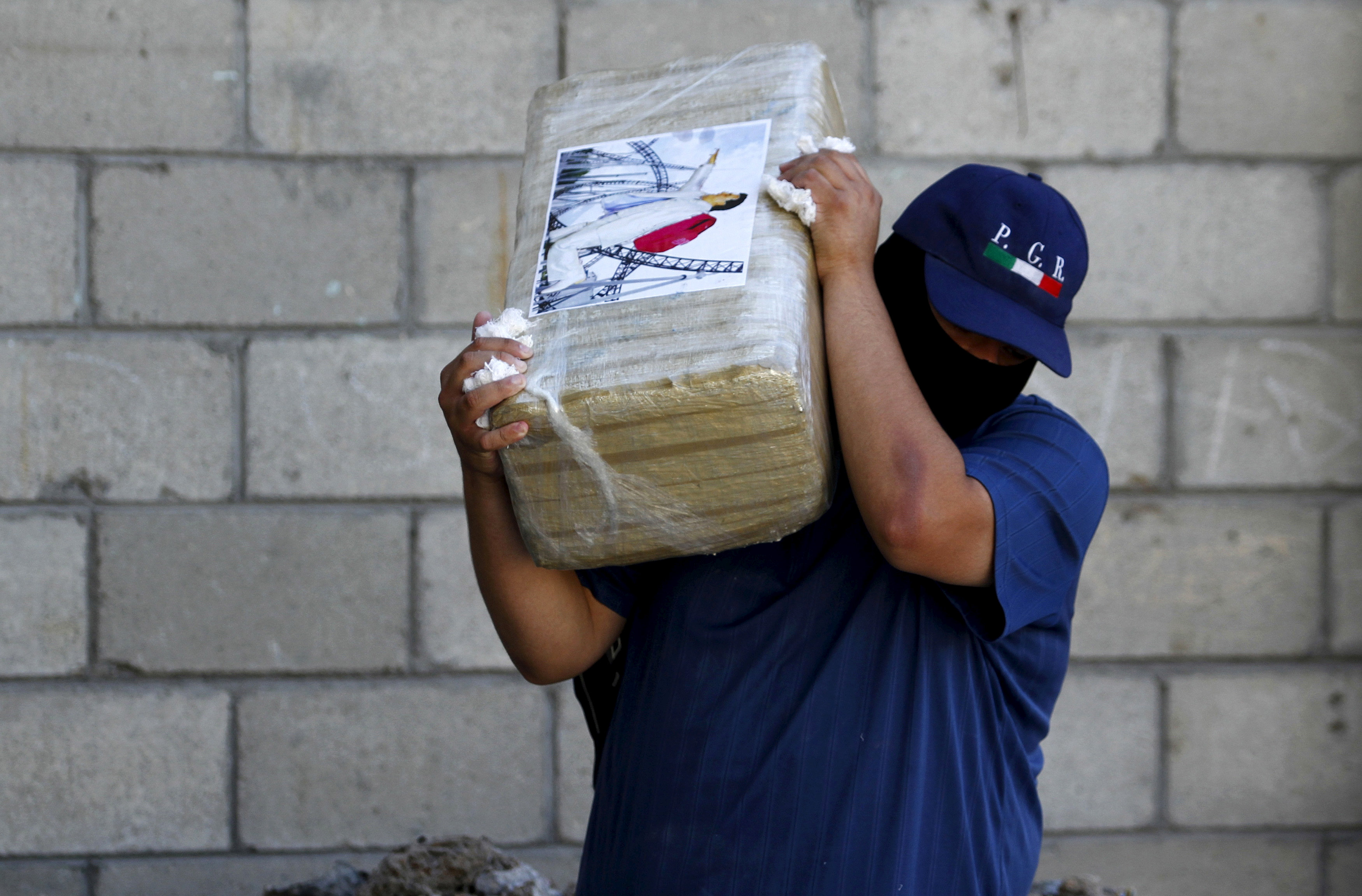 "FILE PHOTO: An agent of the office of the Attorney General of Mexico carries a package of seized marijuana at the site of a passageway Mexican authorities on Thursday attributed to the cartel of fugitive kingpin Joaquin ""El Chapo"" Guzman in Tijuana, October 24, 2015. REUTERS/Jorge Duenes/File Photo"