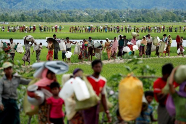 "Rohingya refugees, who crossed the border from Myanmar two days before, walk after they received permission from the Bangladeshi army to continue on to the refugee camps, in Palang Khali, near Cox's Bazar, Bangladesh October 19, 2017. Reuters photographer Jorge Silva: ""This picture was taken after a huge group of people crossed into Bangladesh and then had to wait three days and nights for the Bangladeshi Army's permission to continue walking into the makeshift camps. The line of people seemed endless. Long hours moving slowly across the embankments of the rice field. Mothers with babies and pregnant women, elderly people with illnesses, men carrying their entire life on their shoulders. They were safe from violence, but the challenge of surviving was still waiting for them on this side of the river."" REUTERS/Jorge Silva/File Photo"