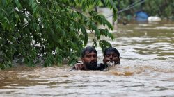 A man rescues a drowning man from a flooded area after the opening of Idamalayr, Cheruthoni and Mullaperiyar dam shutters following heavy rains, on the outskirts of Kochi, India August 16, 2018. REUTERS/Sivaram V