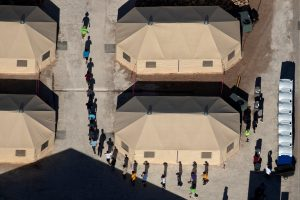 FILE PHOTO: Immigrant children are led by staff in single file between tents at a detention facility next to the Mexican border in Tornillo, Texas, U.S., June 18, 2018. Picture taken June 18, 2018. REUTERS/Mike Blake/File Photo