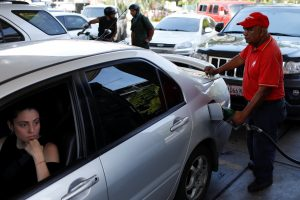 A gas station worker pumps gas into a car at a gas station of the Venezuelan state-owned oil company PDVSA in Caracas, Venezuela August 17, 2018. REUTERS/Marco Bello