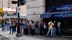 People line up to withdraw cash from an automated teller machine (ATM) outside a Banco Mercantil branch in Caracas, Venezuela August 17, 2018. REUTERS/Marco Bello