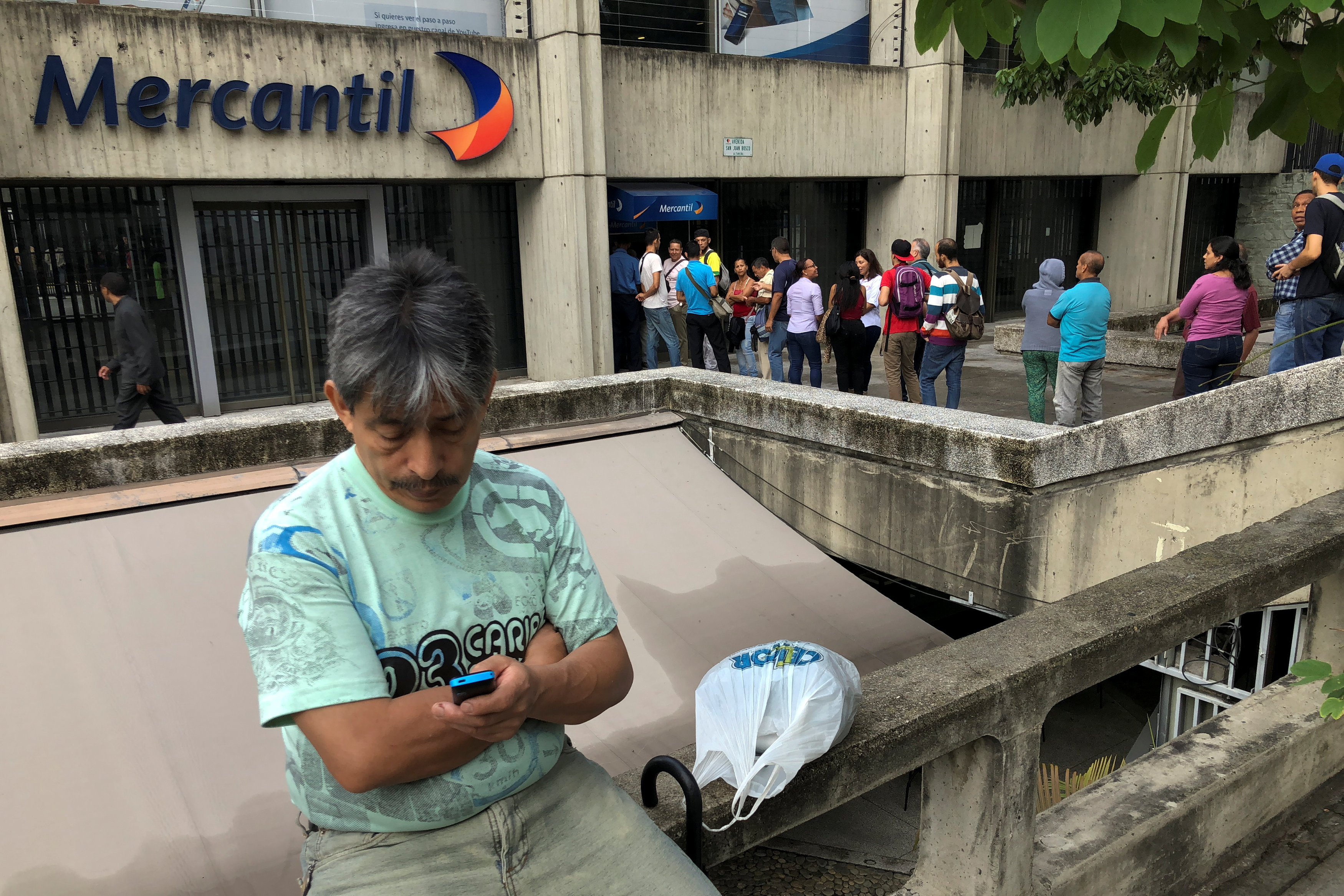 People queue to withdraw cash from automated teller machines (ATM) at a Mercantil bank branch in Caracas, Venezuela August 21, 2018. REUTERS/Carlos Garcia Rawlins