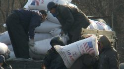 FILE PHOTO - Workers unload food aid from a truck in the Sinuiju region of North Korea in this picture taken on December 11, 2008 from a tourist boat on the Yalu River, which divides North Korea and China. REUTERS/Stringer/File Photo