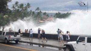 Incoming waves tower over bystanders in Kona, Hawaii, U.S. August 23, 2018 in this still image from video obtained from social media. Ryan Leinback/via REUTER
