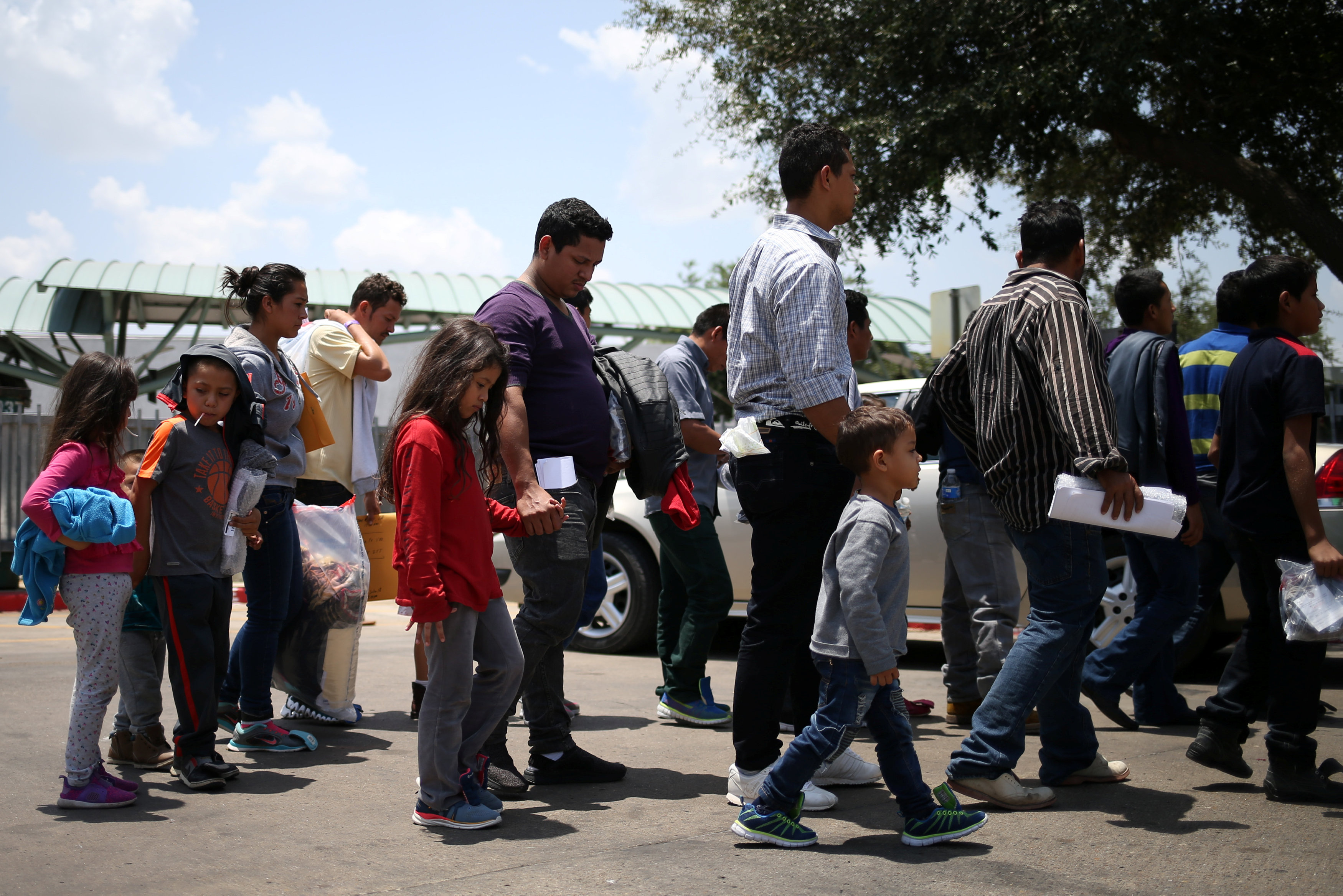FILE PHOTO - Undocumented immigrant families walk from a bus depot to a respite center after being released from detention in McAllen, Texas, U.S., July 26, 2018. REUTERS/Loren Elliott