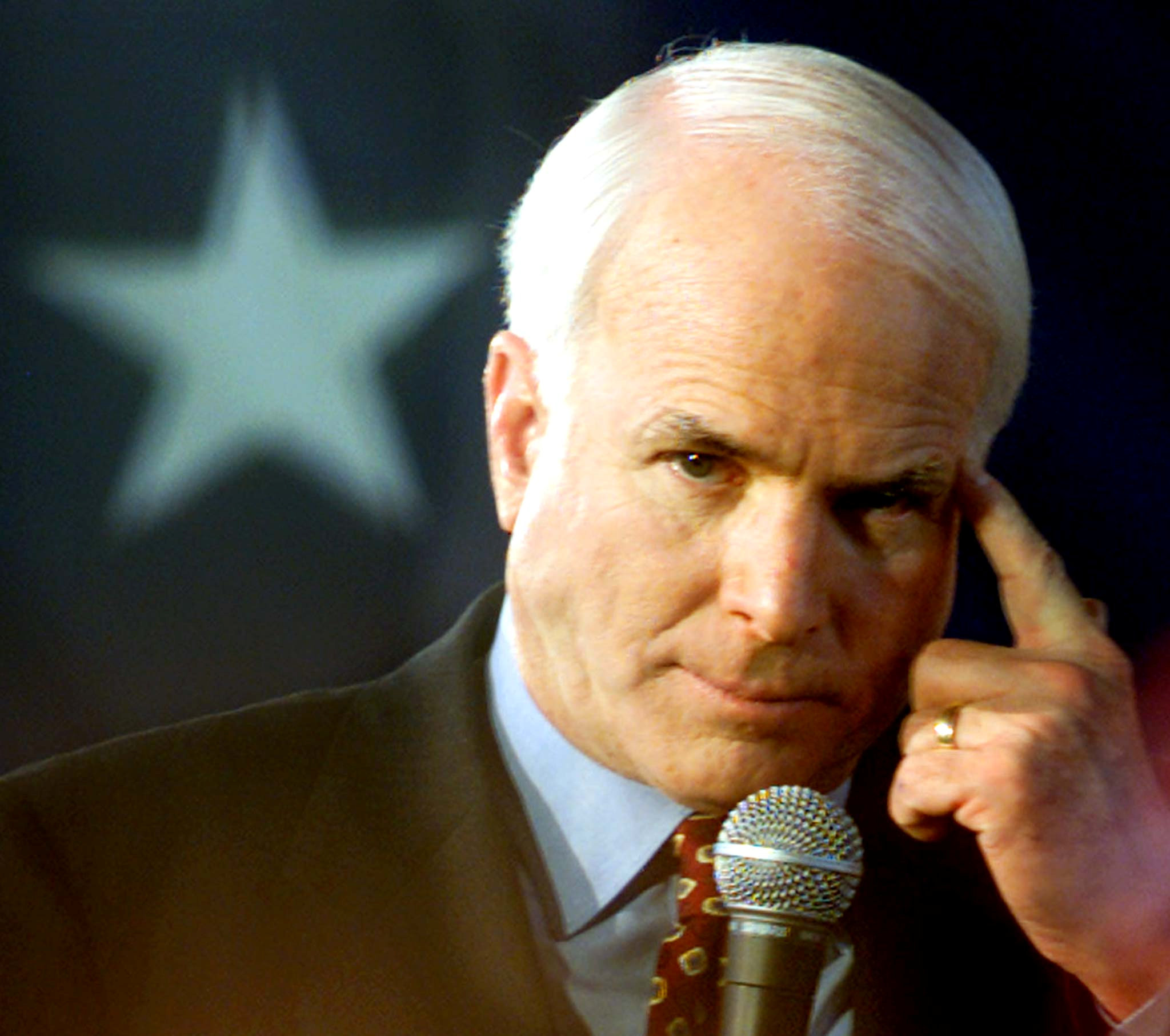 FILE PHOTO - Republican presidential hopeful John McCain points to his head during his Carolina kickoff rally at Presbyterian College February 2, 2000. REUTERS/Kevin Lamarque/File Photo