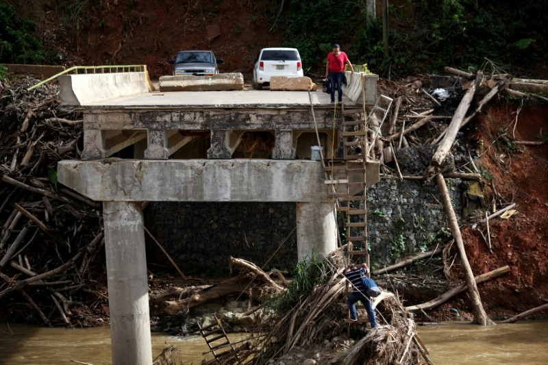 FILE PHOTO: A woman looks as her husband climbs down a ladder at a partially destroyed bridge, after Hurricane Maria hit the area in September, in Utuado, Puerto Rico, November 9, 2017. REUTERS/Alvin Baez/File Photo