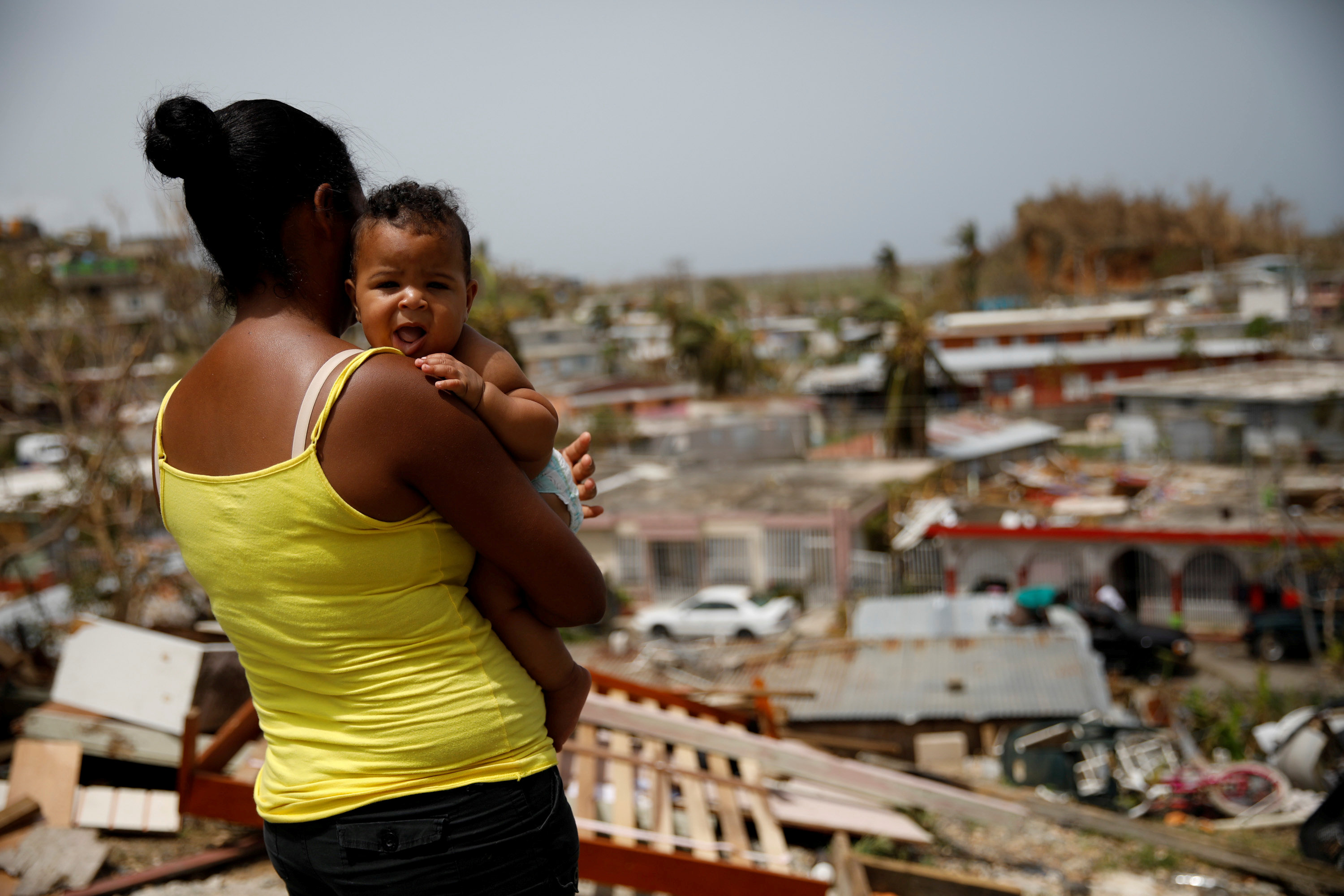 FILE PHOTO: Ysamar Figueroa carrying her son Saniel, looks at the damage in the neighbourhood after the area was hit by Hurricane Maria, in Canovanas, Puerto Rico September 26, 2017. REUTERS/Carlos Garcia Rawlins/File Photo