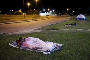 Venezuelan people sleep on the grass in front of interstate Bus Station in Boa Vista, Roraima state, Brazil August 23, 2018. Picture taken Auguist 23, 2018. REUTERS/Nacho Doce
