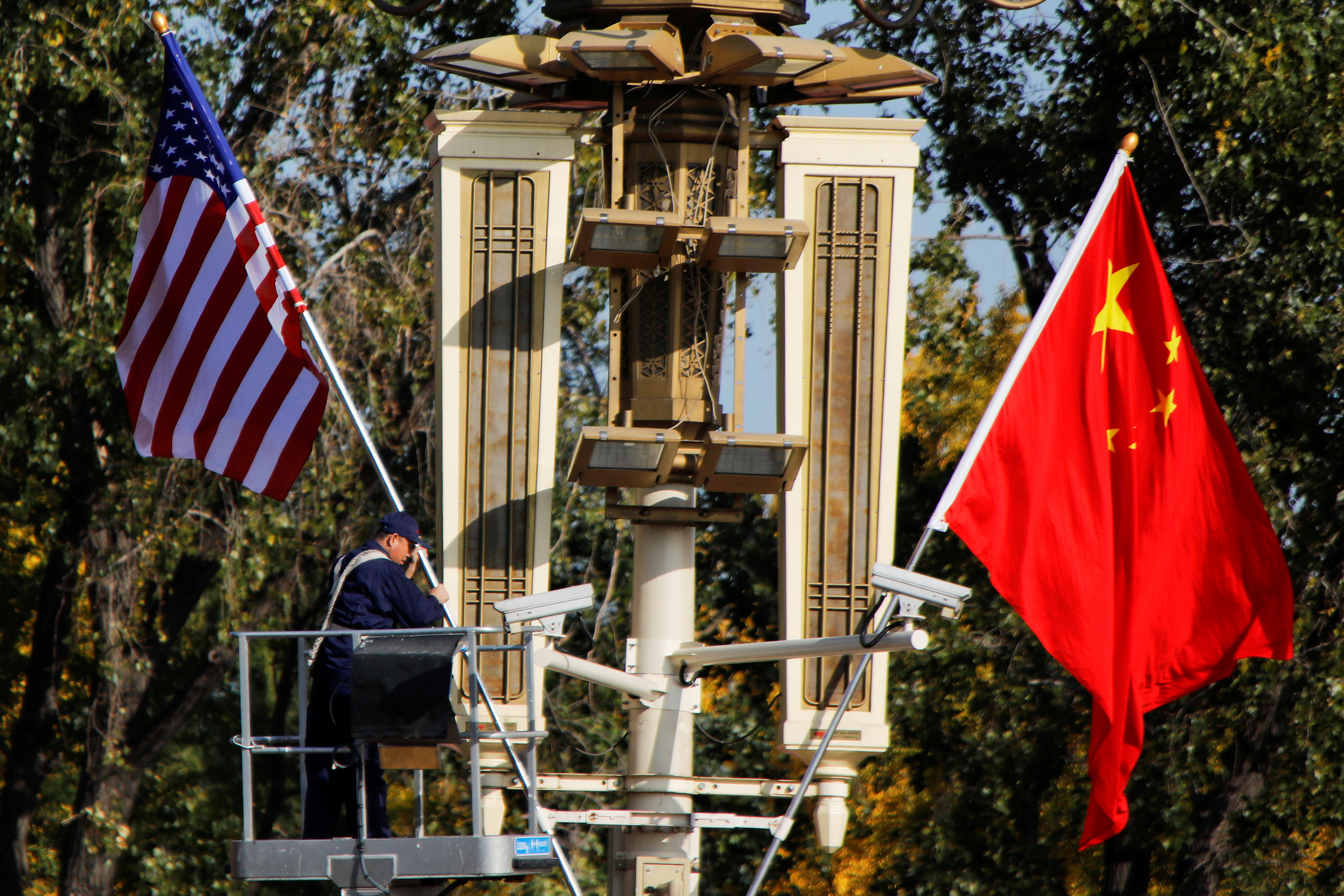 FILE PHOTO: A worker places U.S. and China flags near the Forbidden City ahead of a visit by U.S. President Donald Trump to Beijing, in Beijing, China November 8, 2017. REUTERS/Damir Sagolj/File Photo