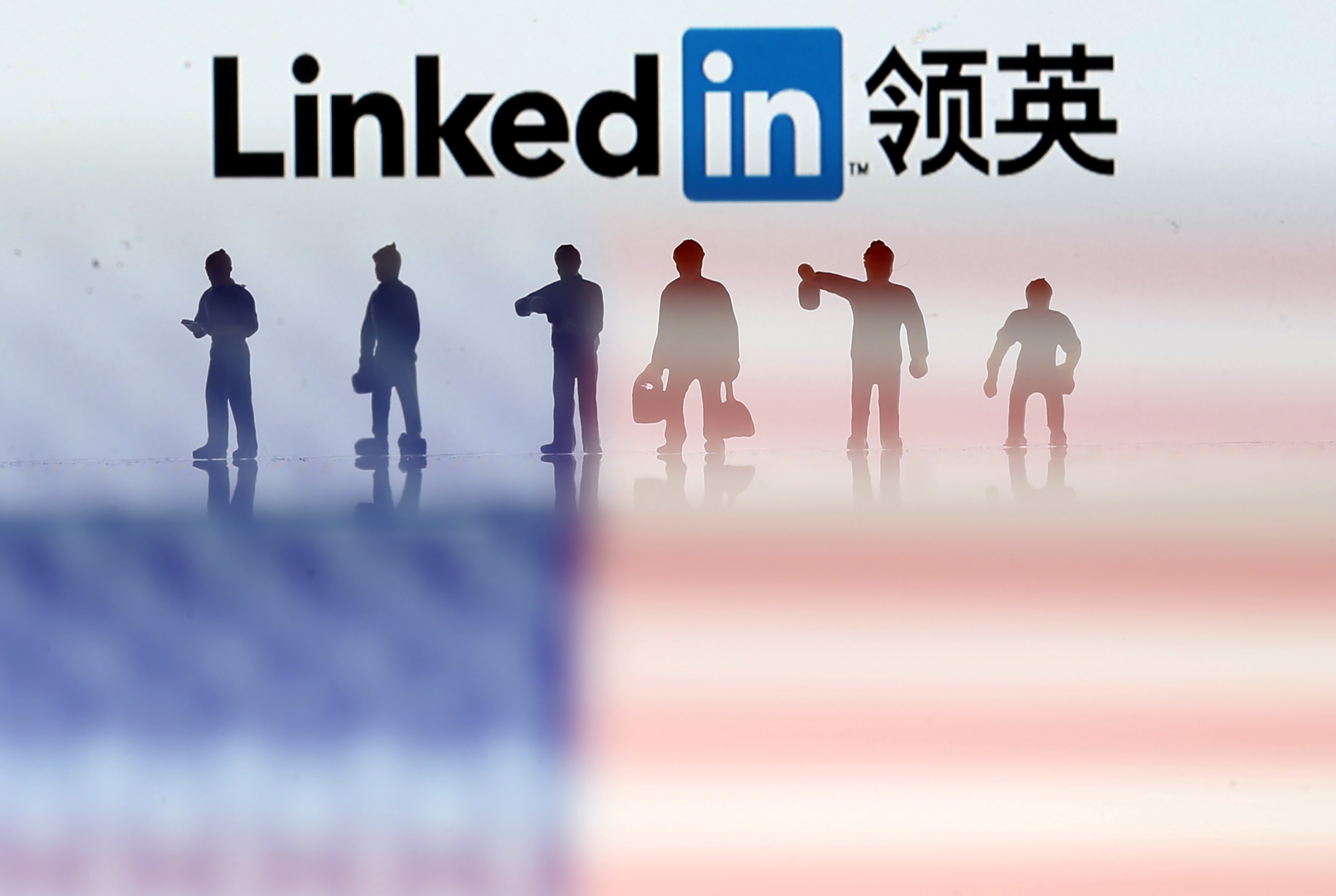 Small toy figures are seen between displayed U.S. flag and Linkedin logo in this illustration picture, August 30, 2018. To match Exclusive LINKEDIN-CHINA/ESPIONAGE REUTERS/Dado Ruvic/Illustration