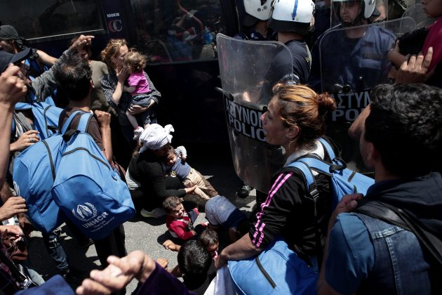 FILE PHOTO: Refugees and migrants from the camp of Moria stand in front of riot police during a protest over the camp's conditions, near the city of Mytilene, on the Greek island of Lesbos, May 26, 2018. REUTERS/Elias Marcou