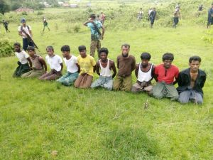 FILE PHOTO: Ten Rohingya Muslim men with their hands bound kneel as members of the Myanmar security forces stand guard in Inn Din village September 2, 2017. REUTERS/File Photo