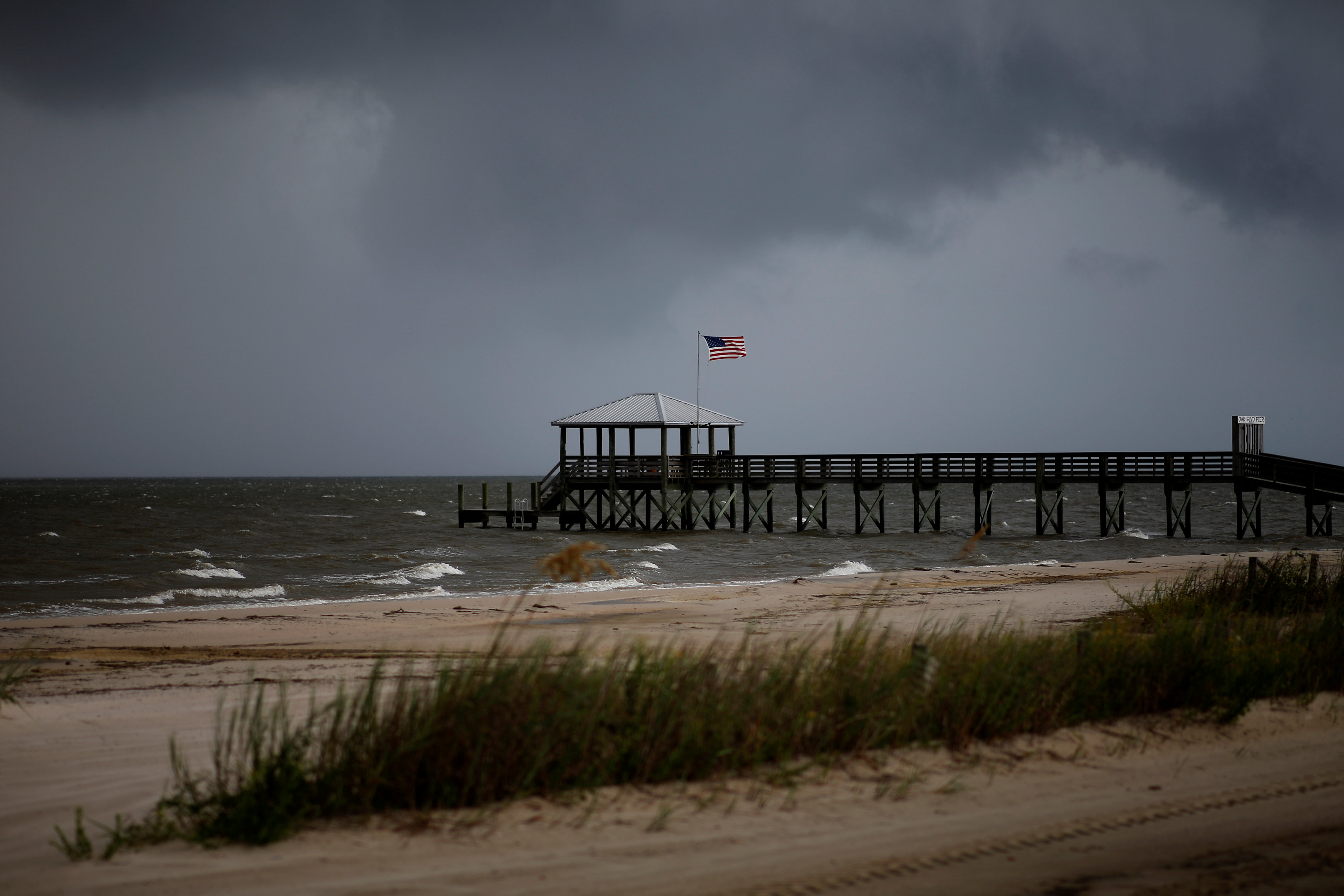 Storm clouds loom over a pier as Tropical Storm Gordon approaches in Waveland, Mississippi, U.S., September 4, 2018. REUTERS/Jonathan Bachman
