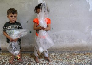 Children hold plastic bags with a paper cup in them, in Idlib, Syria September 3, 2018. REUTERS/Khalil Ashawi
