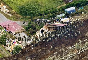 Members of the Japan Self-Defense Forces (JSDF) search for survivors from a house damaged by a landslide caused by an earthquake in Atsuma town, Hokkaido, northern Japan, in this photo taken by Kyodo September 7, 2018. Kyodo/via REUTERS