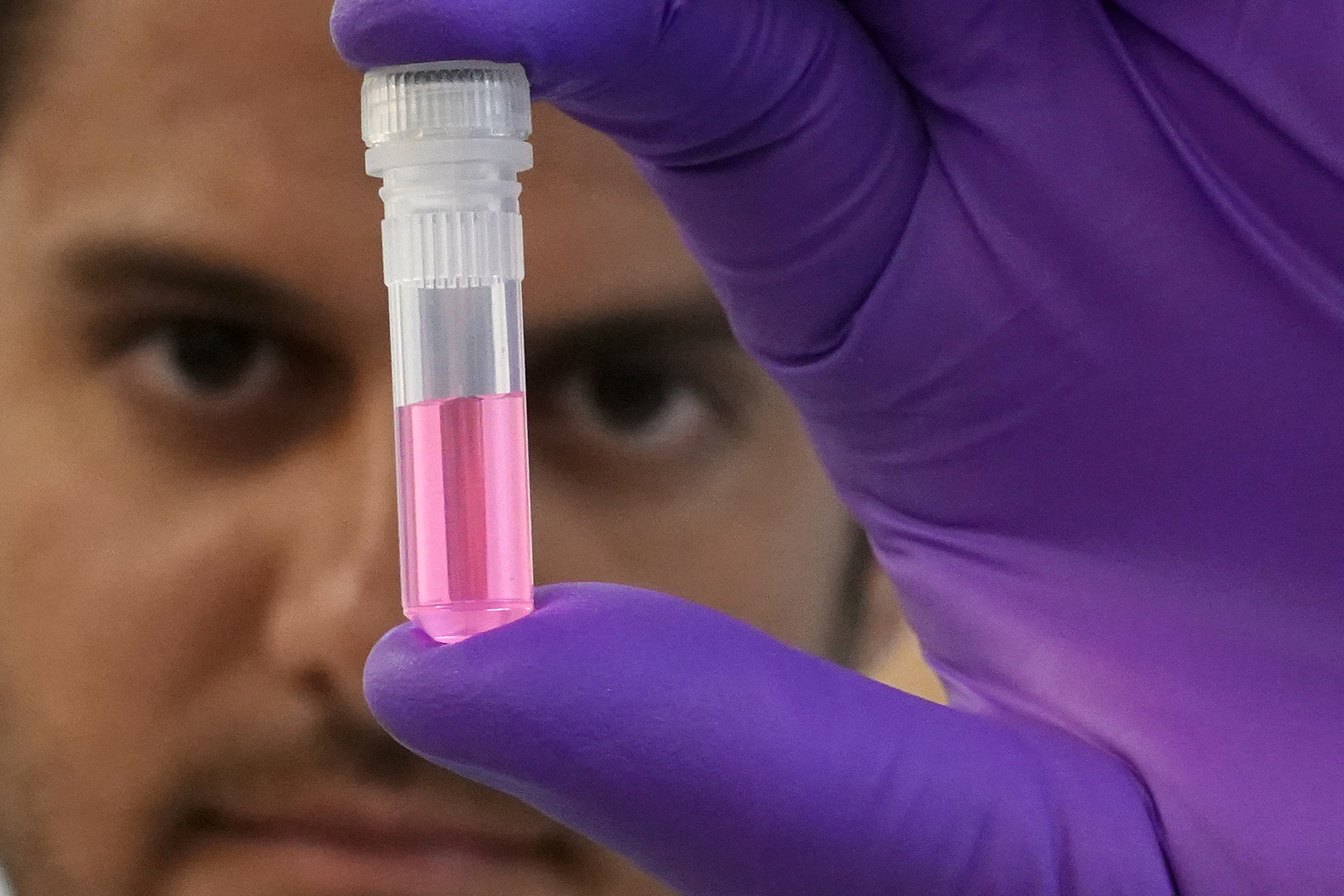 Andrew Schweighardt holds a vial with a DNA sample at the office of the Chief Medical Examiner of New York during an event in New York City, New York, U.S., September 6, 2018. REUTERS/Carlo Allegri