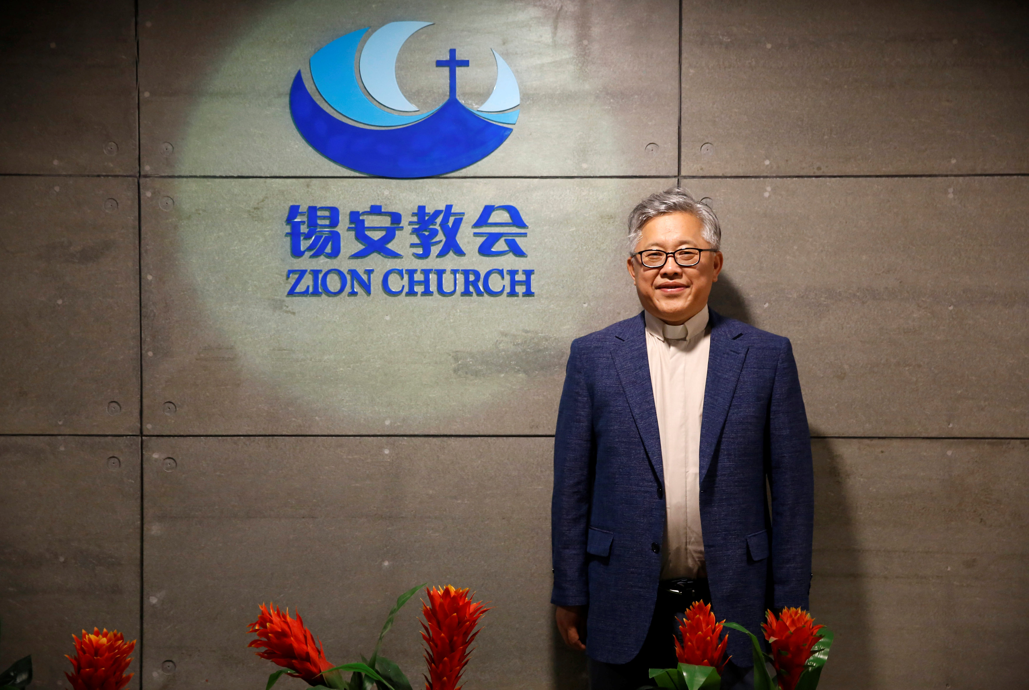 "FILE PHOTO: The head pastor of the Zion church in Beijing Jin Mingri poses for picures in the lobby of the unofficial Protestant ""house"" church in Beijing, China, August 28, 2018. Picture taken August 28, 2018. REUTERS/Thomas Peter"
