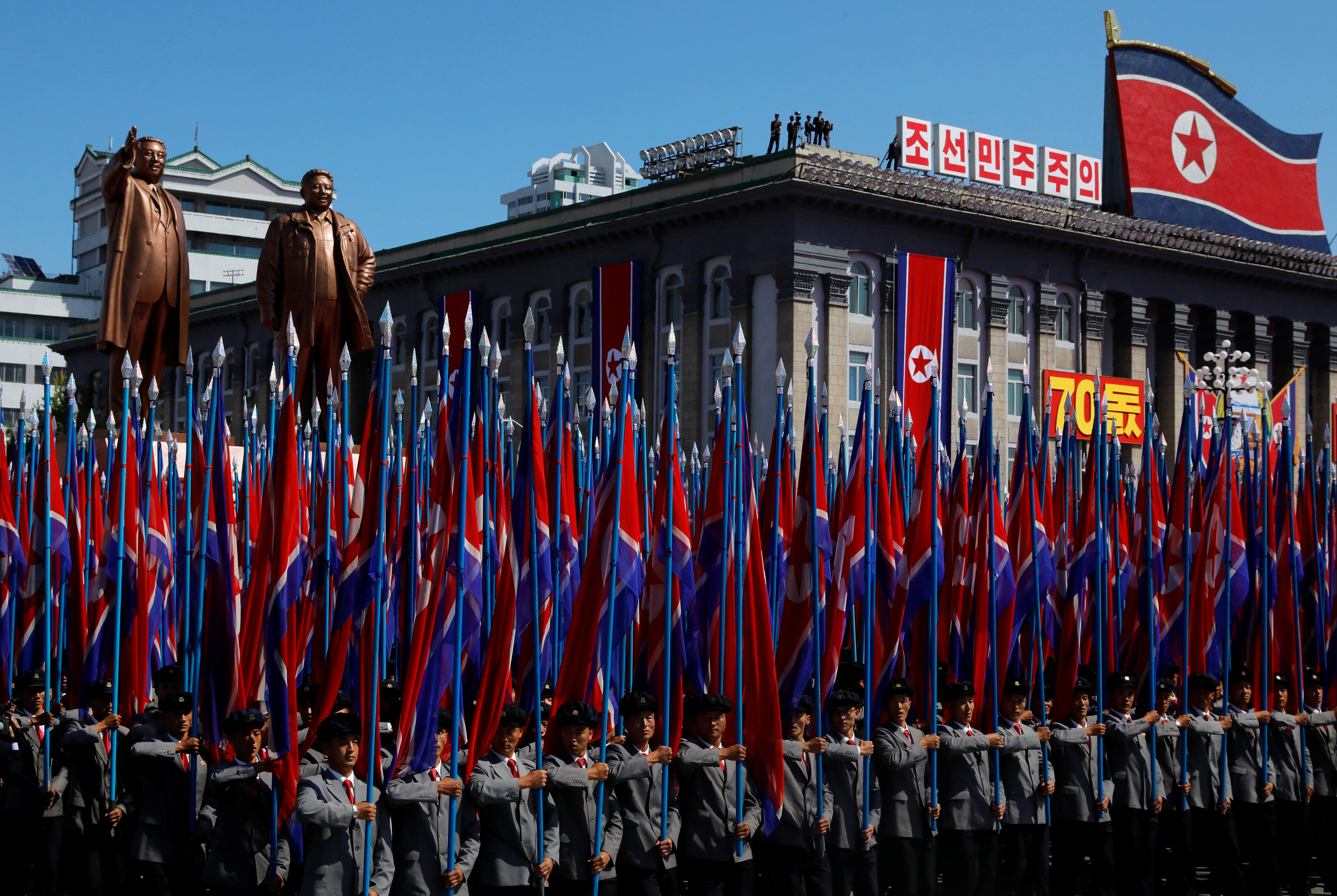 People carry flags in front of statues of North Korea founder Kim Il Sung (L) and late leader Kim Jong Il during a military parade marking the 70th anniversary of North Korea's foundation in Pyongyang, North Korea, September 9, 2018. REUTERS/Danish Siddiqui