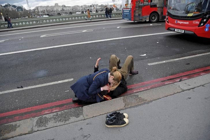 FILE PHOTO: A woman assists an injured person after an incident on Westminster Bridge in London, Britain, March 22, 2017. REUTERS/Toby Melville/File photo