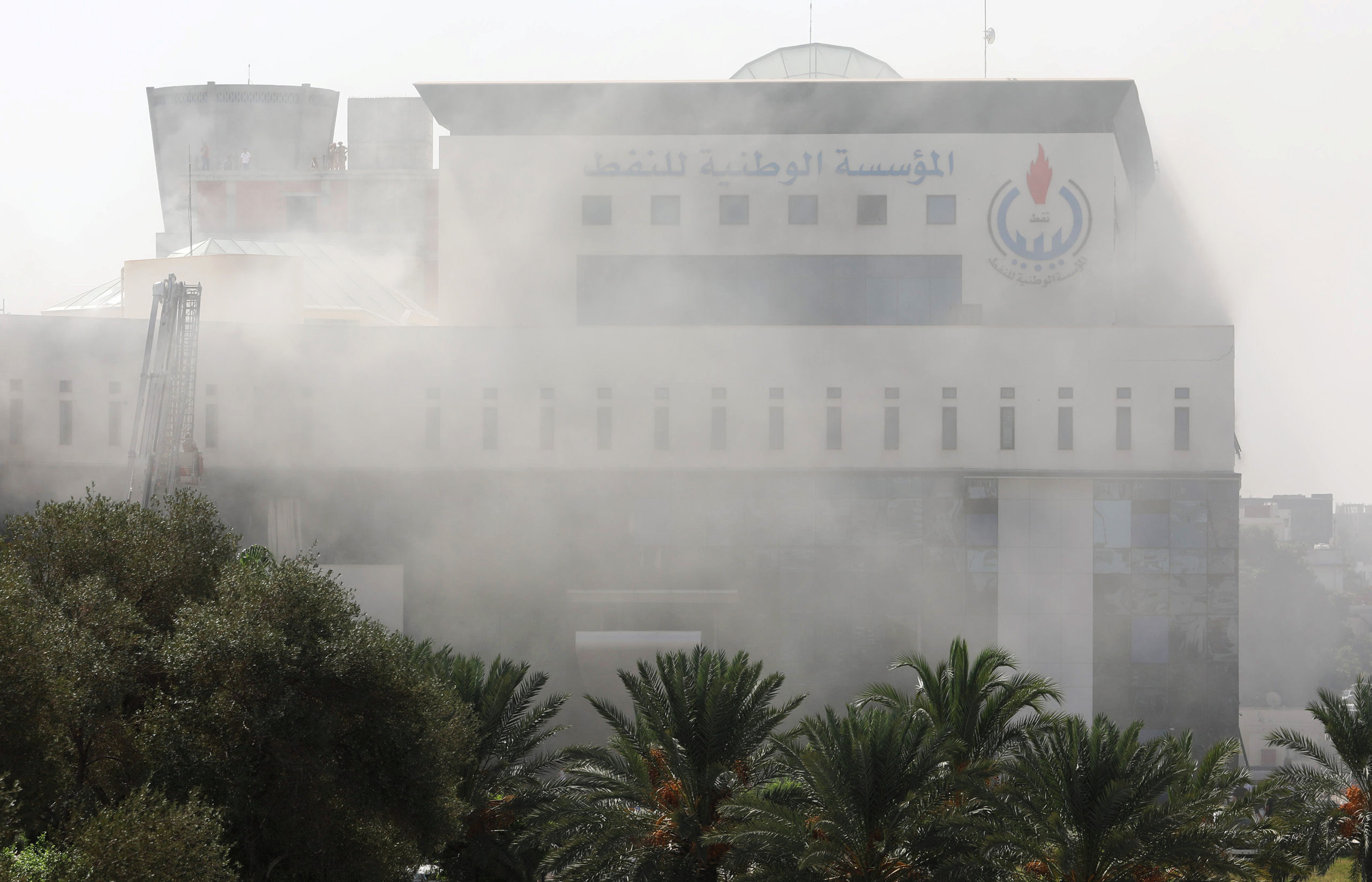 Smoke rises form the headquarters of Libyan state oil firm National Oil Corporation (NOC) after three masked persons attacked it in Tripoli, Libya September 10, 2018. REUTERS/Hani Amara