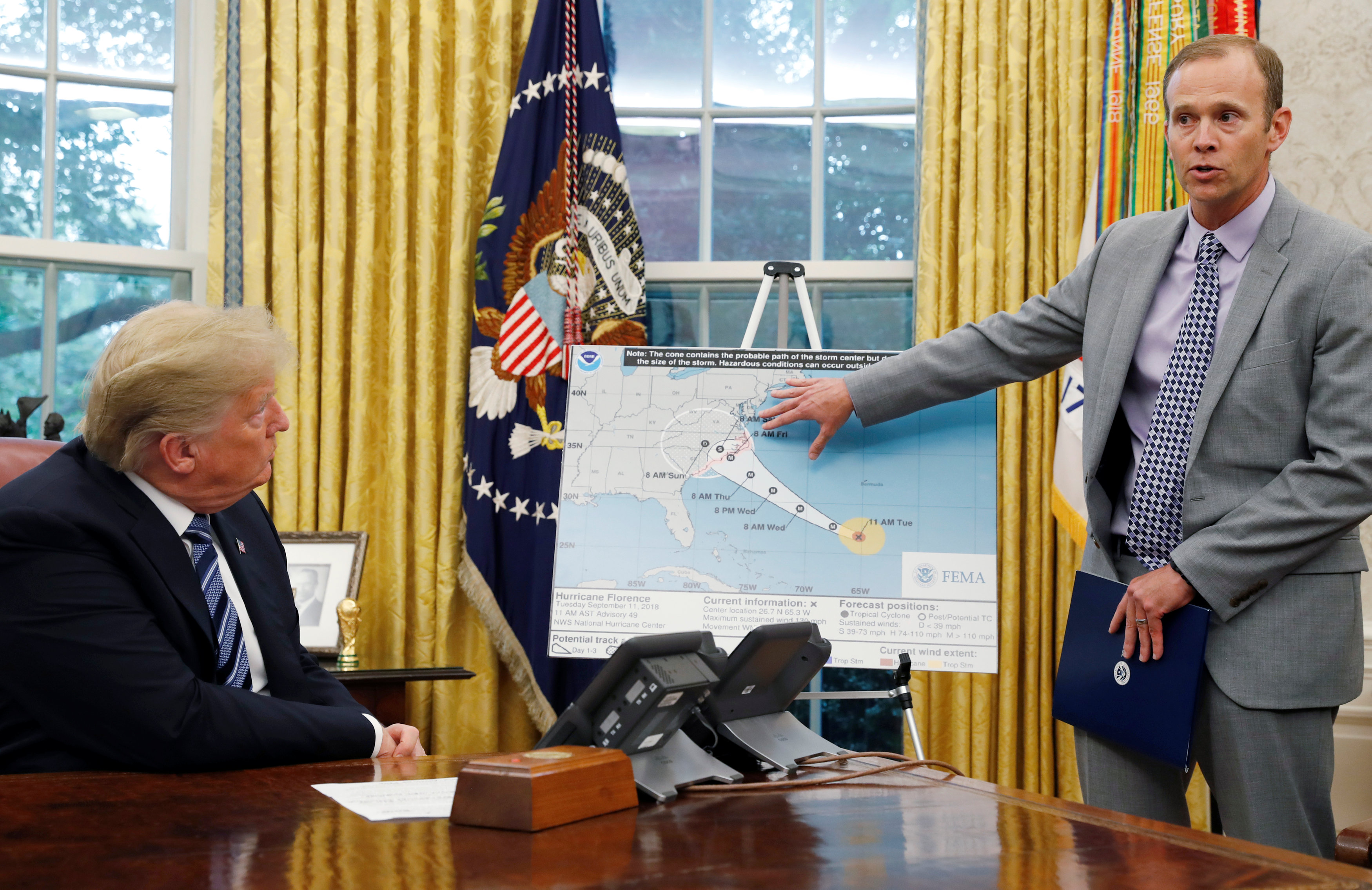 U.S. President Donald Trump holds an Oval Office meeting on hurricane preparations as FEMA Administrator Brock Long points to the potential track of Hurricane Florence on a graphic at the White House in Washington, U.S., September 11, 2018. REUTERS/Leah Millis
